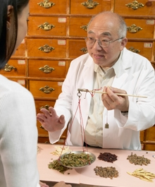 Chinese Herbalist showing herbs to a customer - Doctor Mosaraf Ali